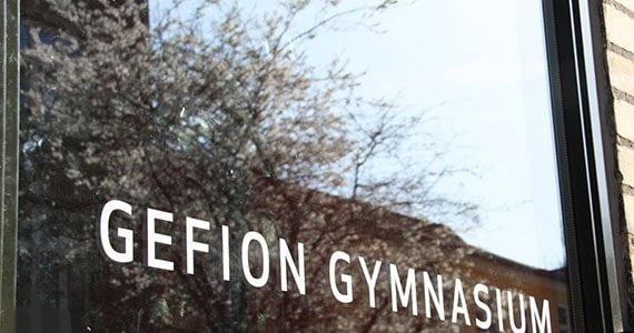 Glasdør ved indgangen til Gefion Gymnasium hvor blomstrende træer spejler sig i ruden