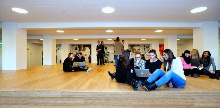 Grupper af elever der sidder på gulvet omkring en bærbar computer