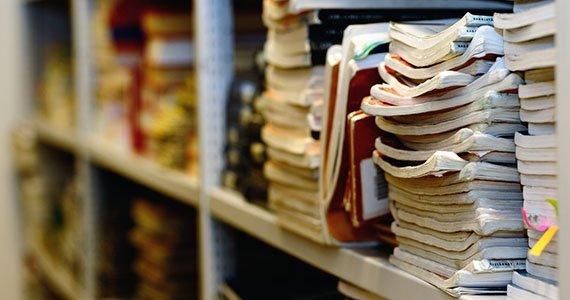 Bøger der ligger i stakke på hylder