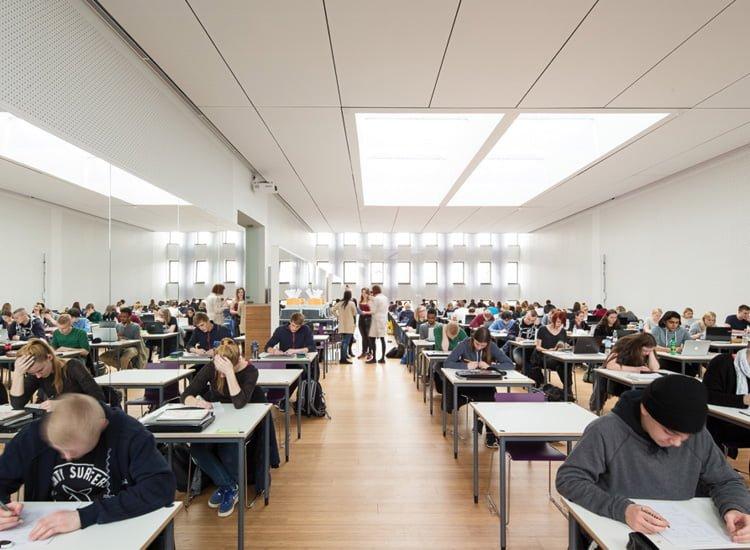 Elever sidder i rækker til eksamen i en stor sal