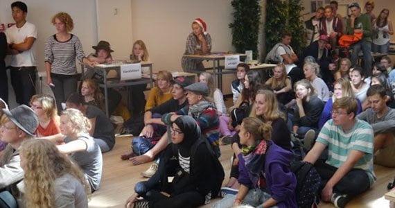 Elever sidder på gulvet i salen og lytter