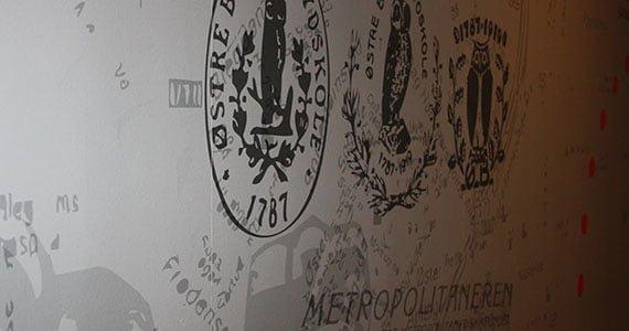 Væg på Gefion Gymnasium med gamle monogrammer fra Metropolitanskolen og Østre Borgerdyd Gymnasium malet på.