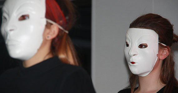 To elever med hvide masker på
