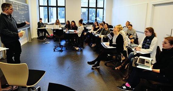 Elever der sidder på stole i rundkreds og modtager undervisning