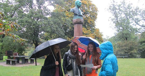 Elever med paraply foran buste i park i regnvejr