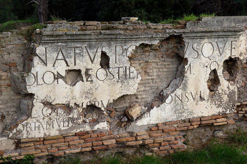 Forfalden mur med latinske inskriptioner