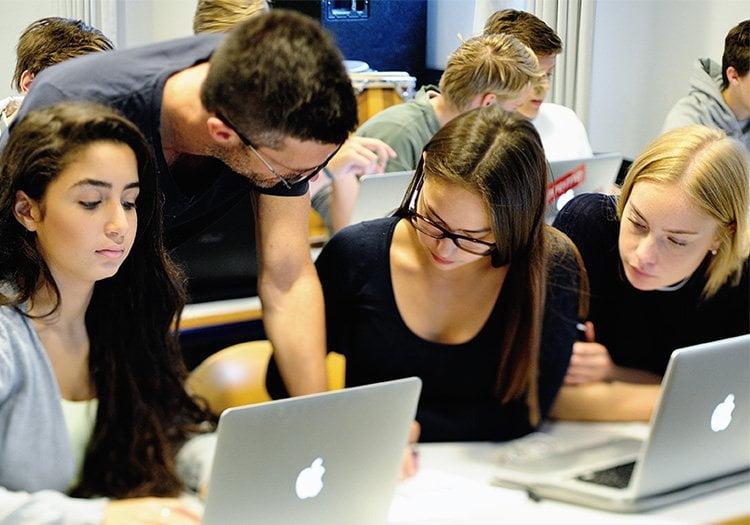 Lærer der er ved at hjælpe elev, der arbejder på sin bærbare computer