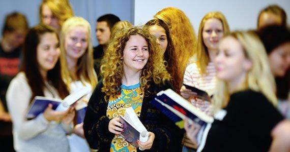 Elever der står op i klasselokalet med sangbøger