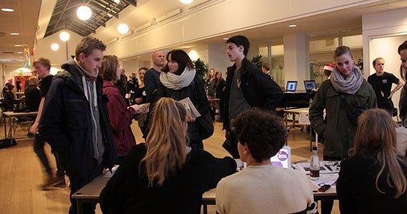 Elever går rundt ved borde i stor sal til orienteringsaften