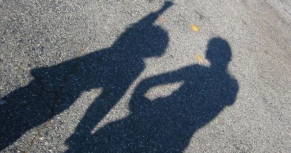 Skygger af to personer på asfalt