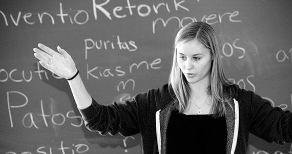 Elev der taler og gestikulerer foran tavle i klasseværelset