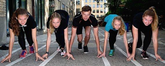 Fem elever i startposition på asfalteret løbebane
