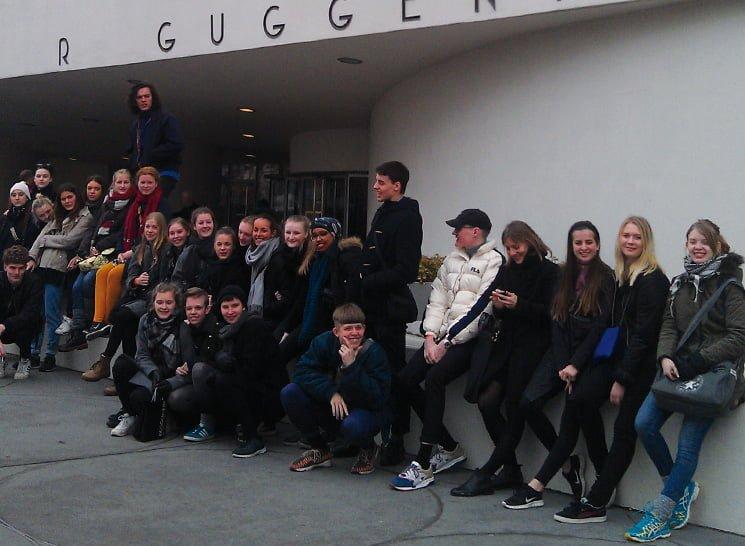 Elever på studietur der står foran bygning og venter