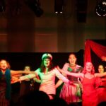 Syngende og dansende elever i kostumer under forestilling