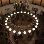 Lærere, elever og besøgende samlet i rotunden, foto taget oppefra med kig ned gennem den store loftslampe