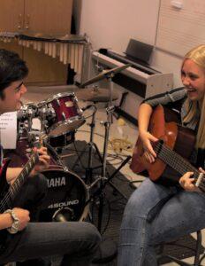 To elever der sidder overfor hinanden og spiller guitar