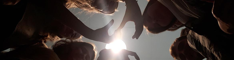 Elever i silhouet der laver tegn med hænderne set nedefra mod solen