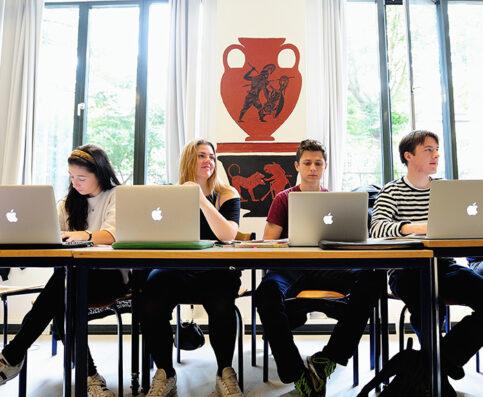 Fire elever i klasseværelset siddende bag hver deres bærbare computer