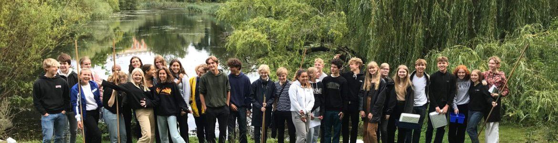 Gruppebilleder af elever der står foran å med fiskenet